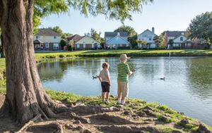 two kids fishing in a pond with houses in the background