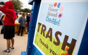 Keep Flower Mound Beautiful Trash sign with trash bin in background