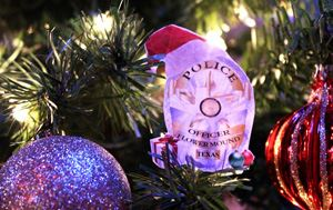 Flower Mound Police Department police badge hanging in a Christmas tree with ornaments around it