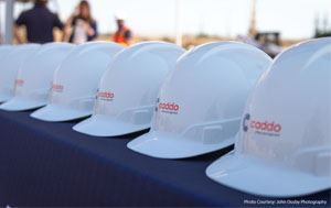 "construction hats that say ""Caddo"" lined up in a row"