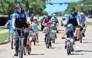 Flower Mound officers riding on bikes with children down a road